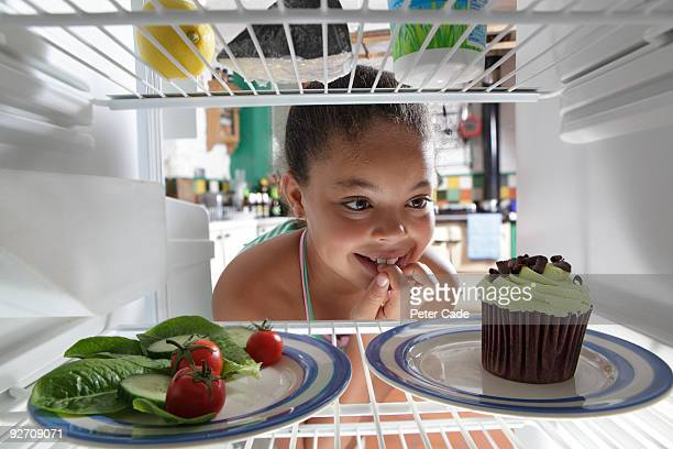 girl choosing between salad and cake