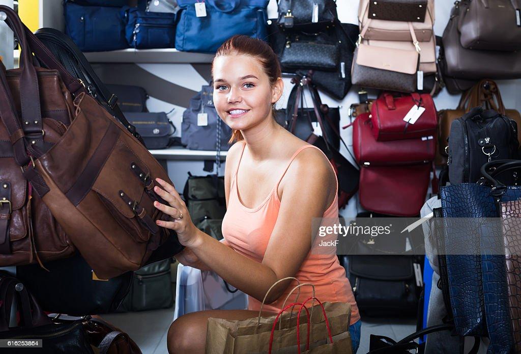 girl choosing handbag in store : Stock Photo