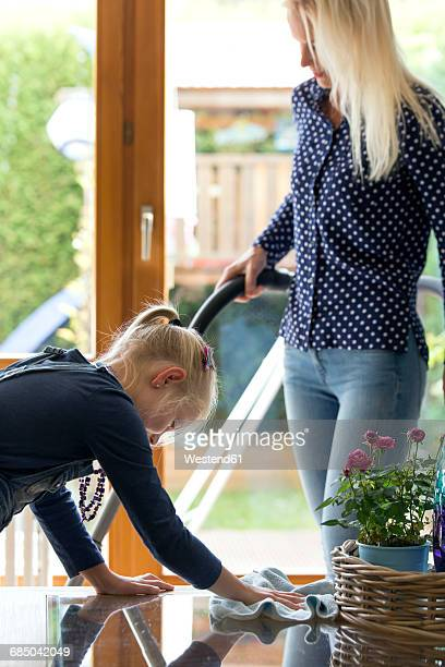 Girl cleaning glass table while her mother hoovering