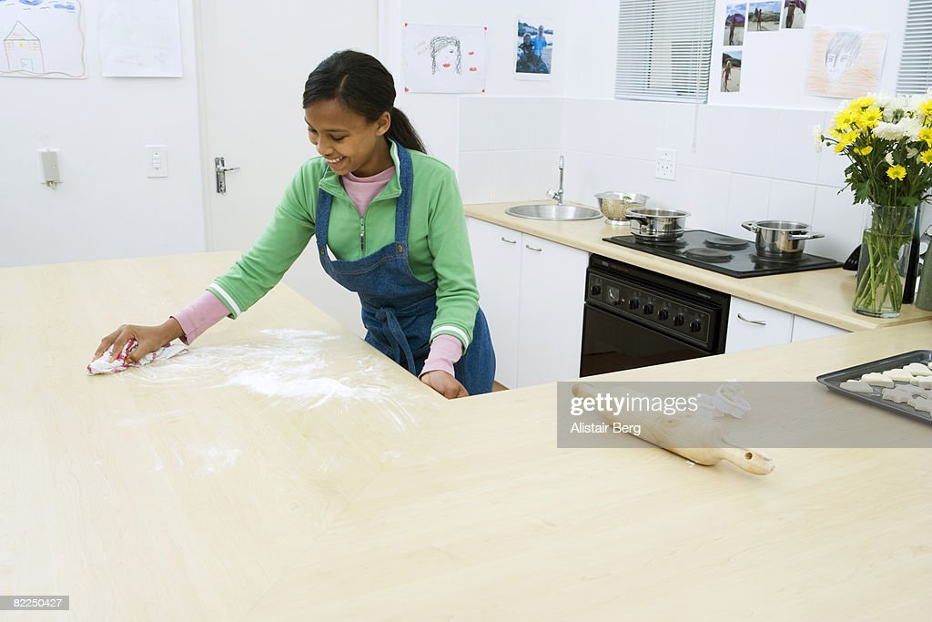Girl cleaning kitchen counter  : Stock Photo