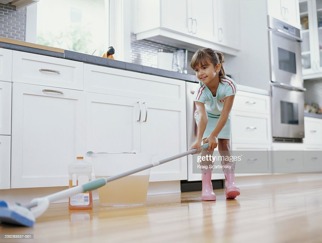 Girl (6-8) cleaning kitchen floor with mop, smiling, low angle view : Stock Photo