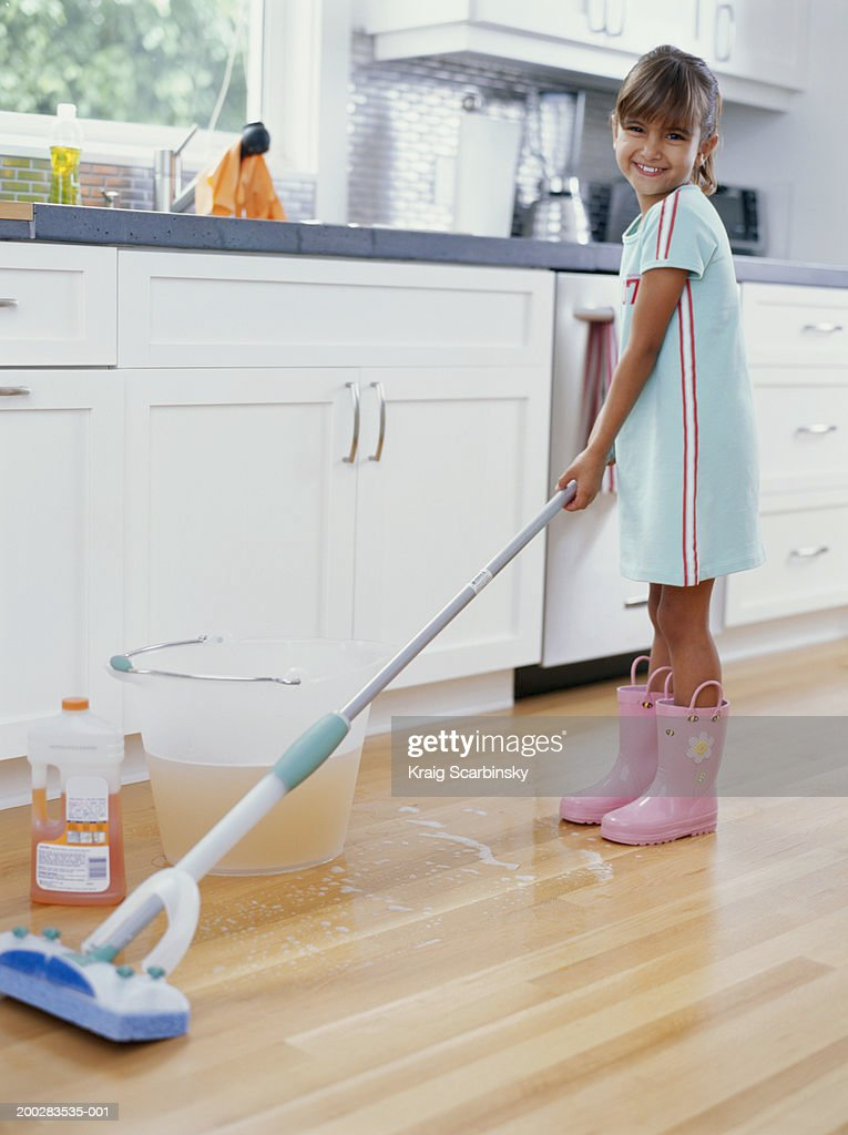 Girl (6 8) Cleaning Kitchen Floor With Mop, Smiling, Portrait :