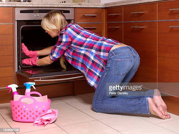 Girl cleaning out kitchen oven