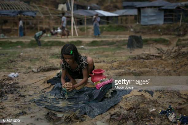Girl cleans clothes with water from a hole that the surrounding households use for washing, drinking, cooking and bathing in the Balukhali camp on...