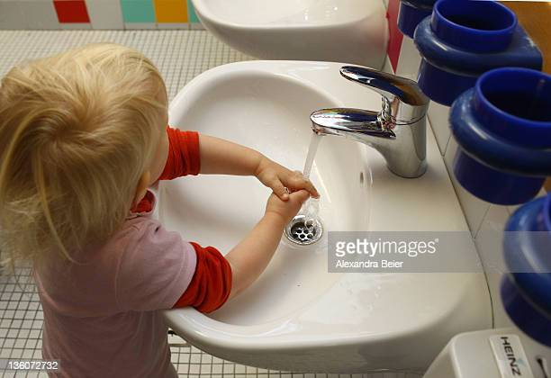A girl cleans her hands at a day care center for children aged 12 months to six years on December 22 2011 in Munich Germany German authorities claim...