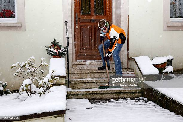 girl clearing the snow in front of house