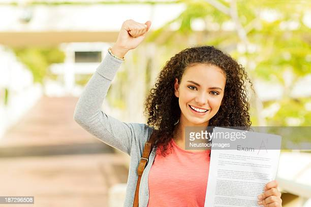 Girl Clenching Fist While Holding Result On College Sidewalk