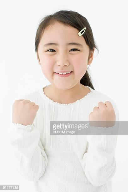 Girl clenching fists, portrait, studio shot