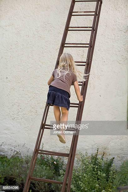A girl climbing a ladder Gotland Sweden.