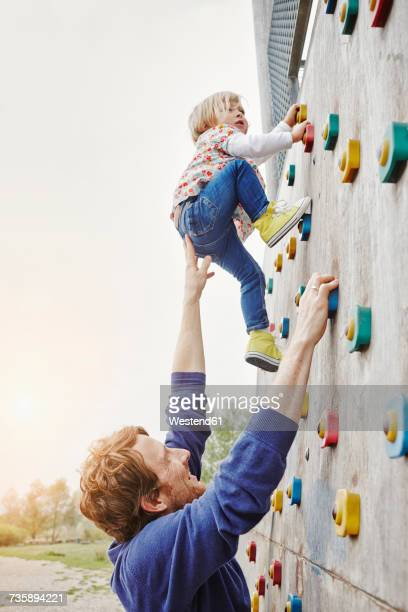 girl climbing on a wall supported by father - beschützer stock-fotos und bilder
