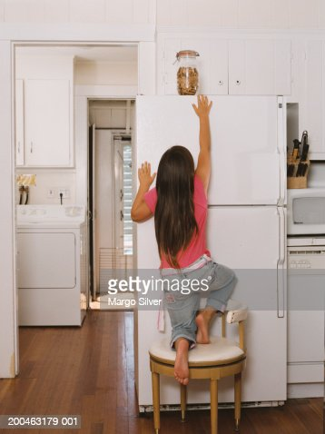 Girl Climbing On Chair Reaching For Cookie Jar Rear View