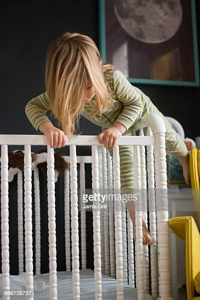 Girl (2-3) climbing on crib