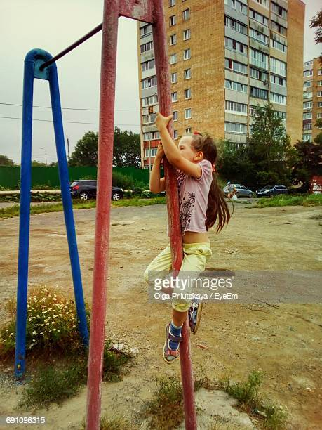 Girl Climbing On Metal Pole At Playground Against Residential Building