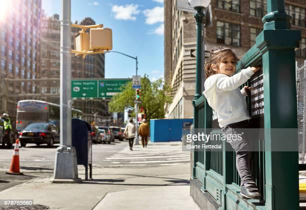 Girl climbing on rail of NYC subway entrance