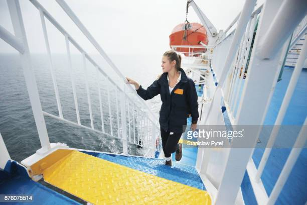 Girl climbing stairs on ferry looking at ocean