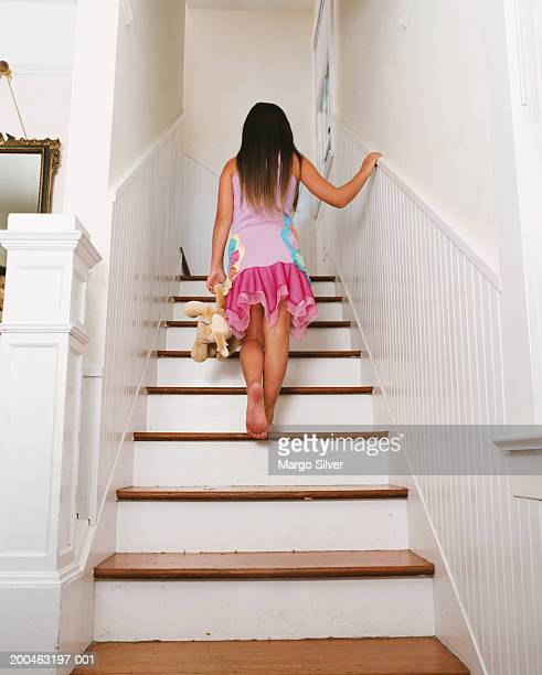 Girl (6-8) climbing stairs with teddy bear, rear view
