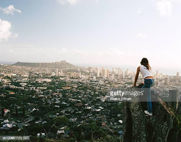 Girl (12-13) climbing stump overlooking cityscape, rear view