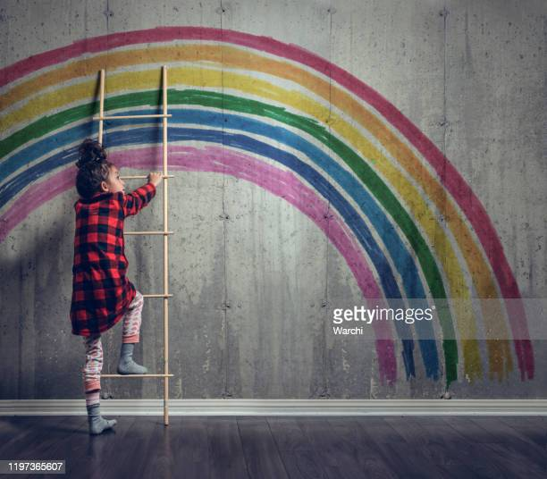 girl climbing to reach the rainbow - climbing stock pictures, royalty-free photos & images