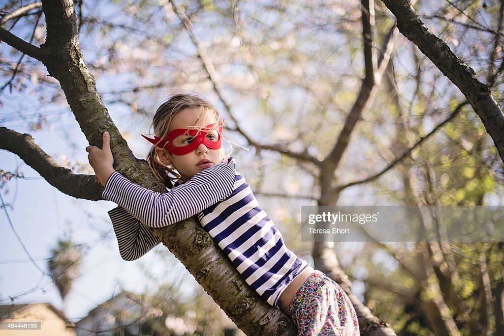 Girl Climbing Tree and Wearing Mask : Stock Photo