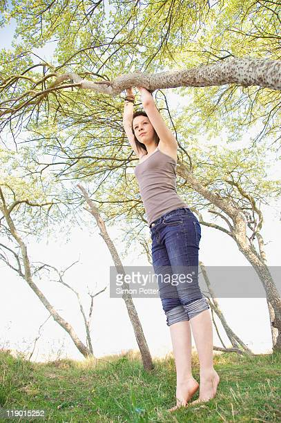 girl climbing tree outdoors - 13 years old girl in jeans stock photos and pictures