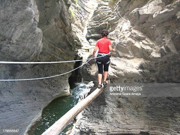 Girl climbing Via ferrata Sorrosal Waterfall in Broto . At the foot of the Ordesa National Park is the via ferrata of Sorrosal. Artfully mounted...