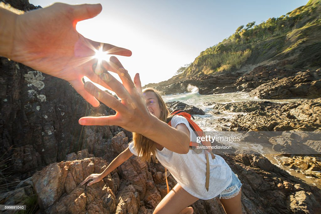 Girl climbs on cliff, partner pulls out hand for assistance : Stock Photo