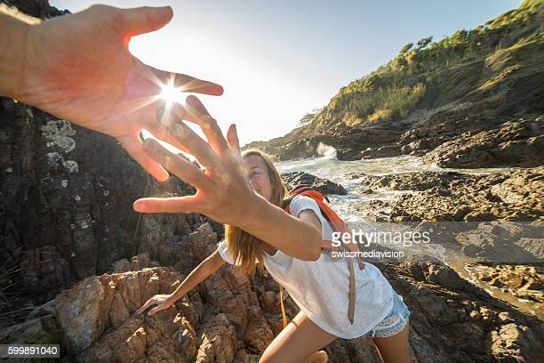 Girl climbs on cliff, partner pulls out hand for assistance