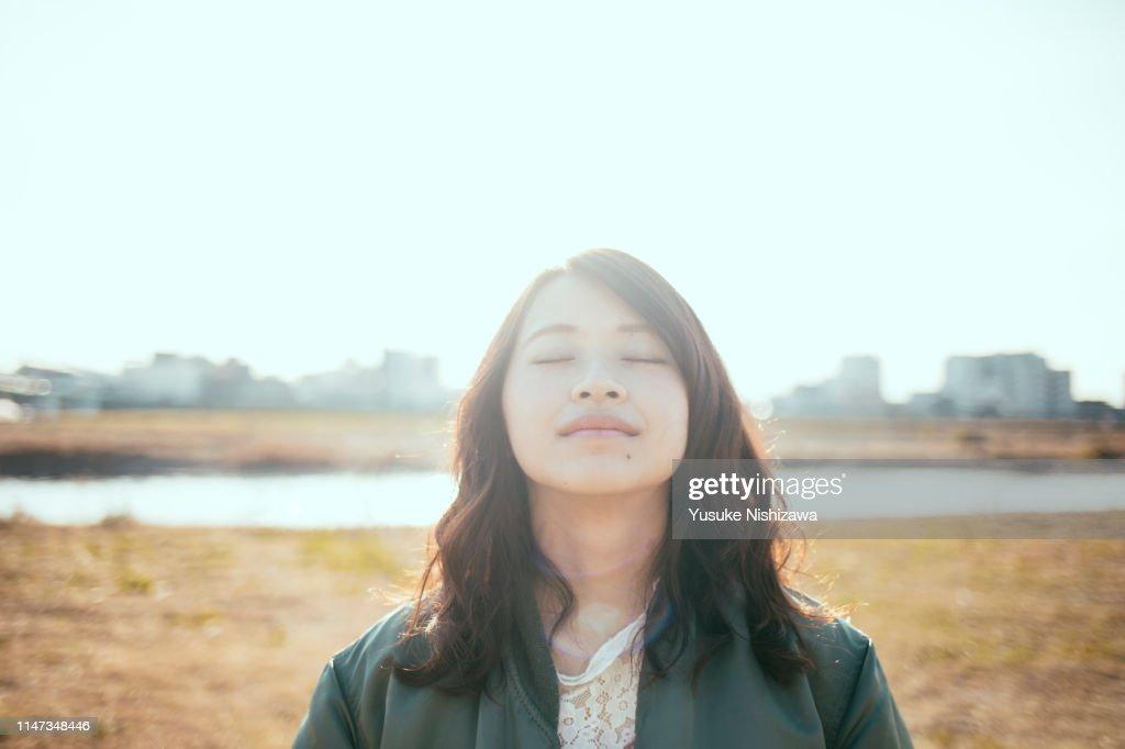Girl closing her eyes at the river bank : ストックフォト
