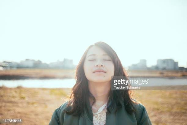 girl closing her eyes at the river bank - serene people stock pictures, royalty-free photos & images