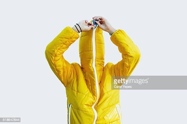 girl closing zipper of yellow raincoat.