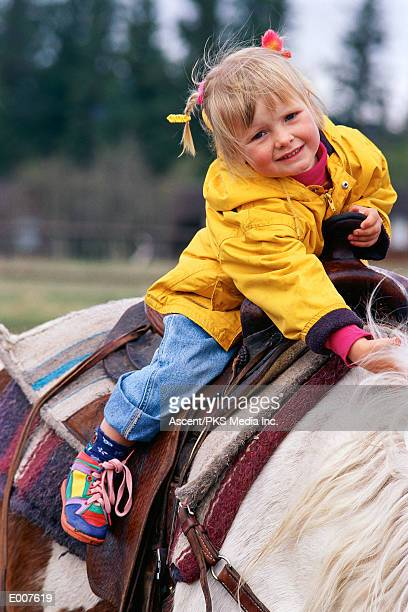 Girl clutching pony's mane and saddle horn