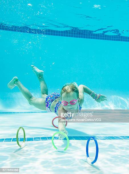 Girl (6-7) collecting diving rings underwater