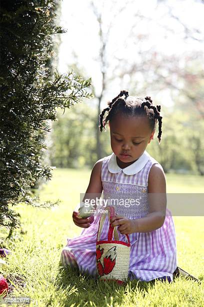 girl (2-4) collecting easter eggs - african american easter stock photos and pictures
