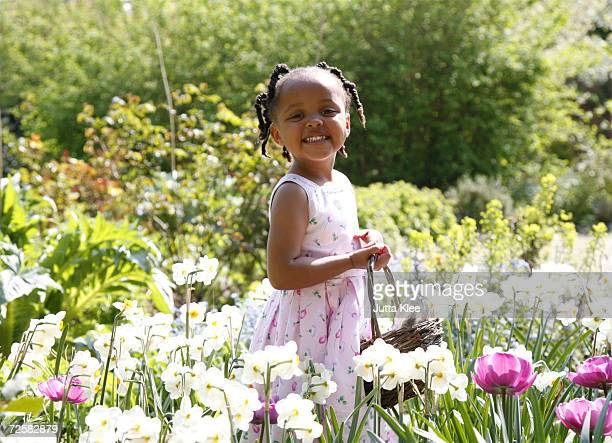 girl (2-4) collecting flowers and easter eggs in garden, smiling - african american easter stock photos and pictures
