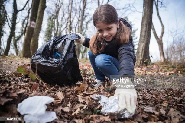 girl collecting litter in the woods - picking up stock pictures, royalty-free photos & images