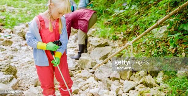 girl picking up trash using garbage