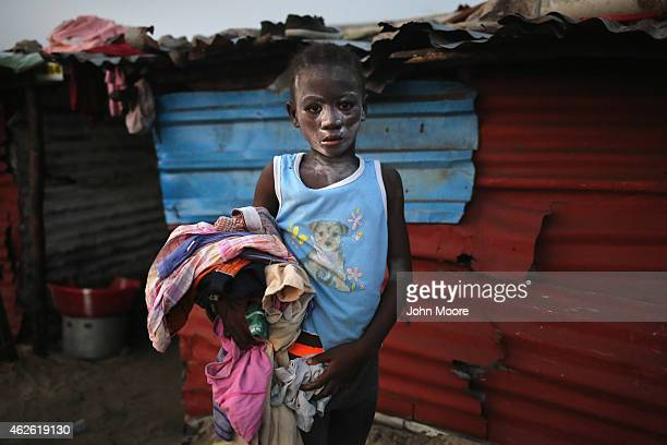 A girl collects her family's laundry after drying it on a rooftop in the West Point township on January 31 2015 in Monrovia Liberia Life has slowly...