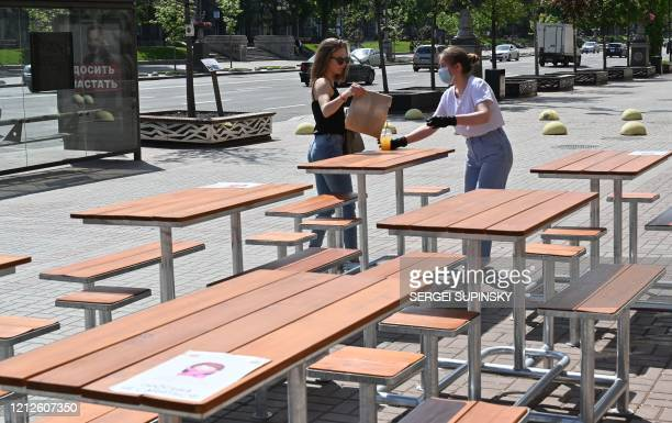 A girl collects her order outside a cafe in Kiev on May 11 as Ukraine partially lifts some restrictions imposed to curb the spread of the COVID19...