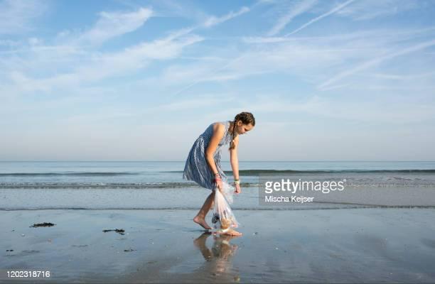 girl collects plastic waste from beach, hoek van holland, netherlands - noord europa stockfoto's en -beelden