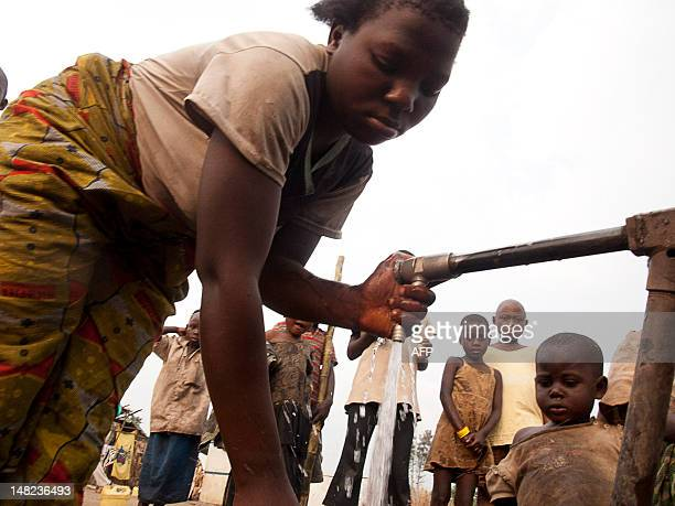 A girl collects water at the refugee camp in Kiwanje amid looting by the Congolese army known as the Armed Forces of the Democratic Republic of Congo...