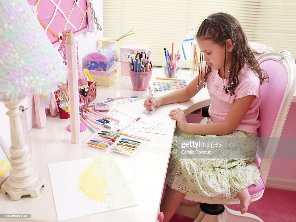 Girl (6-8) coloring at desk in bedroom, side view, close-up : Stock Photo