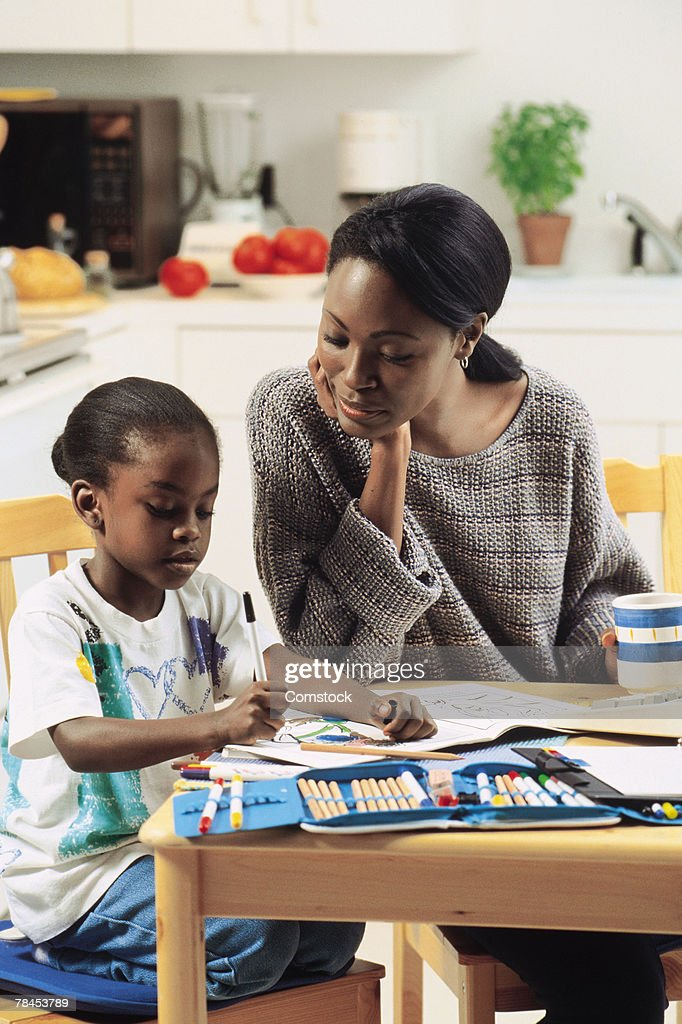 Girl coloring at kitchen table as mother looks on : Stockfoto