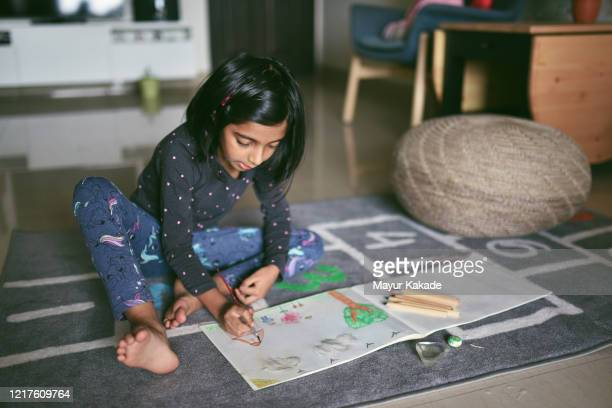 Girl colouring picture at home