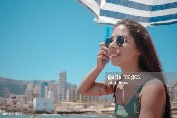 young girl with sunglasses combing her