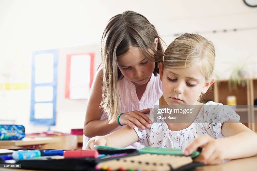 Girl comforting friend in classroom : Stock Photo
