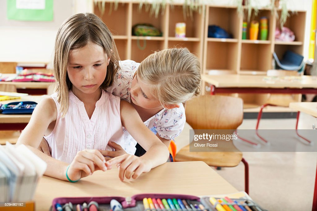 Girl comforting friend in classroom : Stockfoto
