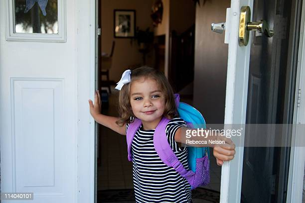 Girl coming out of door with backpack