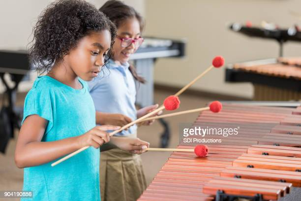 Girl concentrates while playing marimba