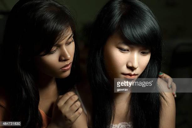 Frau trösten und Ihre traurigen weibliche Mitbewohner unterschiedlicher ethnischer Herkunft.