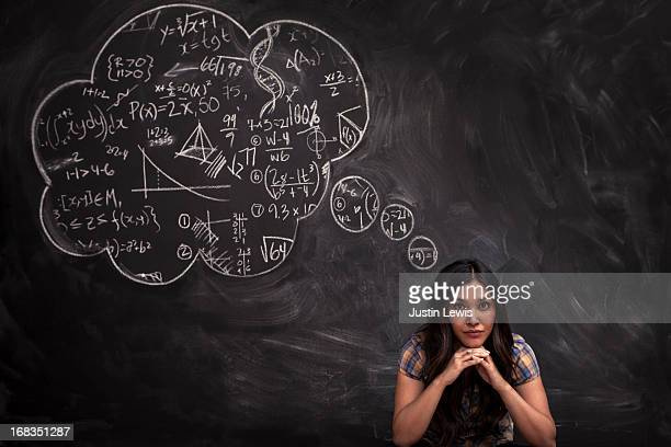Girl contemplates math thought bubble on chalkboar